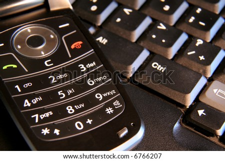 A closeup of a cell phone and a laptop. - stock photo