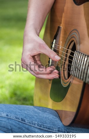 A closeup of a female guitarist with her instrument - stock photo