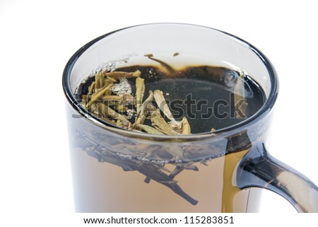 "A closeup of a glass cup of ""Silver Needles"" tea on a white background"