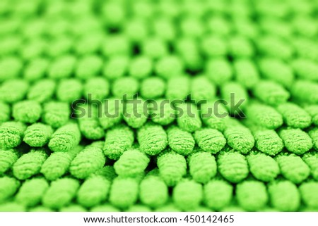 A closeup of a green microfiber carpet for abstract background.