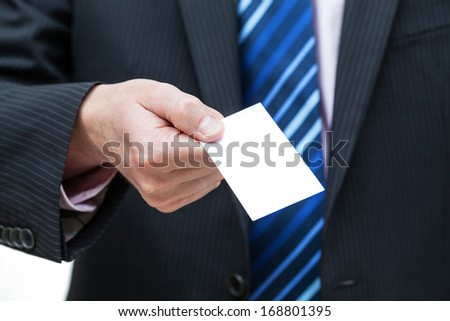A closeup of a hand giving us a business card