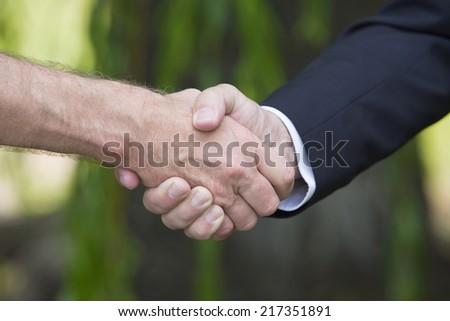 a closeup of a handshake outdoors - stock photo