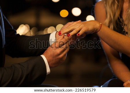 A closeup of a man putting an engagement ring on his girlfriend's hand - stock photo