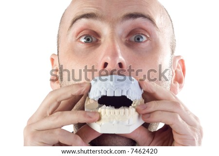 A closeup of a man, raising his eyebrows and playfully holding a model of his mouth to his mouth.