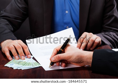 A closeup of a man signing an express cash loan agreement - stock photo