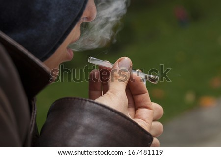 A closeup of a man smoking weed in a short glass pipe - stock photo