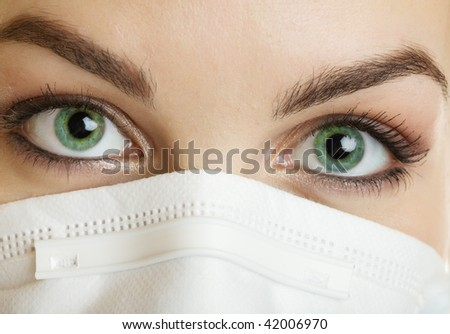 A closeup of a nurse wearing a mask with green eyes