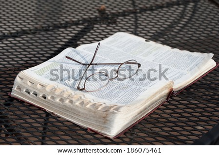A closeup of a pair of reading glasses resting on top of a worn, open Bible on a wrought-iron patio table  - stock photo