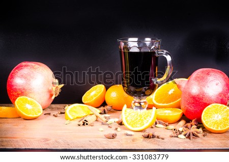 A closeup of a pile of oranges sliced, lemons, pomegranate sliced with spices and juice, wine on wooden, black background. Eating frame. Free space for text. Christmas