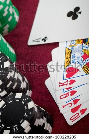 A closeup of a poker hand that just misses getting a Royal Flush. There is straight of hearts-ten, Jack, Queen, King but the Ace is a club with checkered poker chips lined up on the left. - stock photo