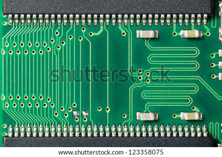 A closeup of a printed circuit board with silver solder points