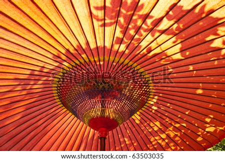 A closeup of a red, Japanese parasol from below with sun shining down - stock photo