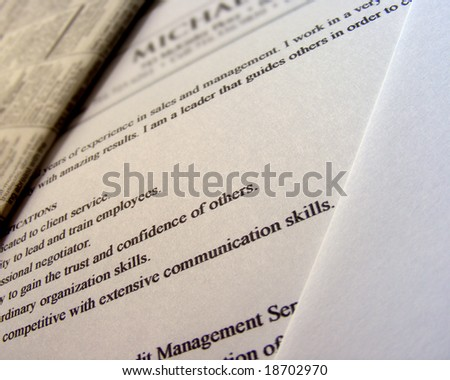 A closeup of a Resume with qualifications in focus. The color usage is a brown. - stock photo