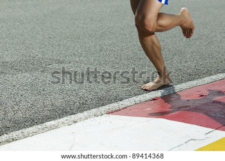 A closeup of a runners feet while barefoot running on a track - stock photo