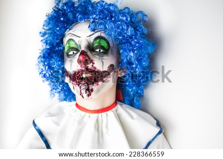A closeup of a scarier clown with sharp pointy teeth glaring at you. Crazy ugly grunge evil clown on Halloween. Scary professional Halloween masks  - stock photo