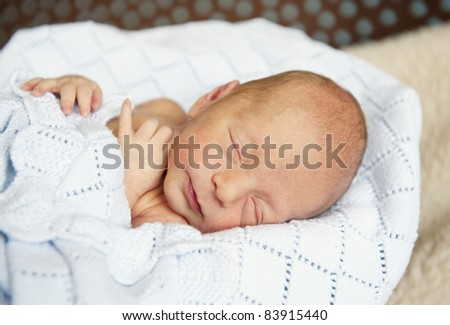 A closeup of a sleeping newborn premature baby boy, focus on his face, studio shot - stock photo