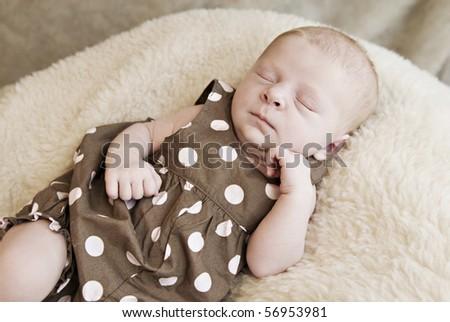 A closeup of a three week old sleeping baby girl, soft focus - stock photo