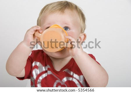 A closeup of a toddler drinking from a cup - stock photo