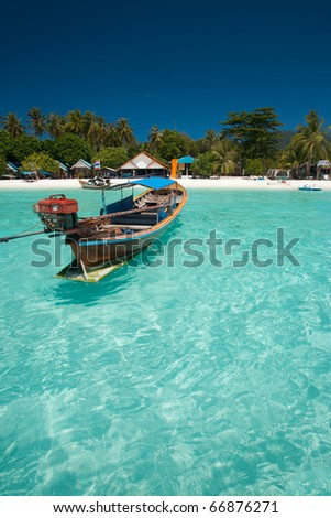A closeup of a traditional Thai longtail boat floating in perfect crystal clear ocean on the island paradise of Ko Lipe, Thailand - stock photo