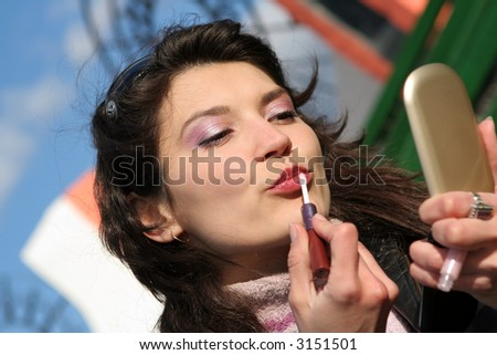 A closeup of a woman putting on lip liner.