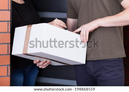 A closeup of a woman signing a package from a mailman - stock photo