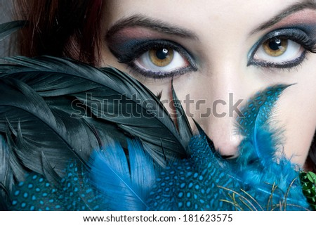 A closeup of a young attractive brunette with hazel eyes hides behind blue feathers while wearing intense makeup and looking into the camera. - stock photo