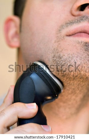 A closeup of a young man shaving his beard off with an electric shaver. - stock photo