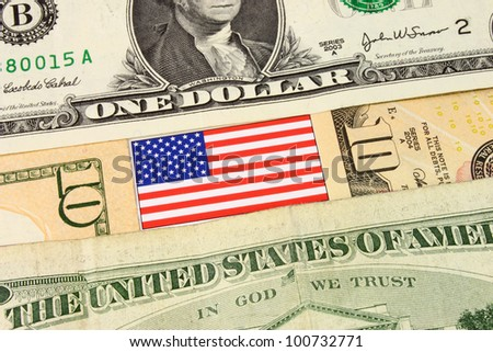 A closeup of American currency bank notes and Stars & Stripes flag. - stock photo