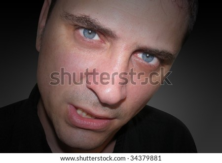 A closeup of an angry man's face. he looks mad, upset and frustrated. There are shadows around his face so the focus is in his eyes. - stock photo