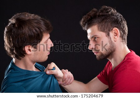 A closeup of an angry man threatening the other by holding his top - stock photo