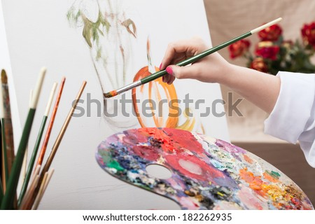 A closeup of an artist with a brush painting a picture - stock photo