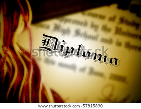 A closeup of an education diploma certificate with a gold color and shadows around it. The word diploma is in focus. - stock photo