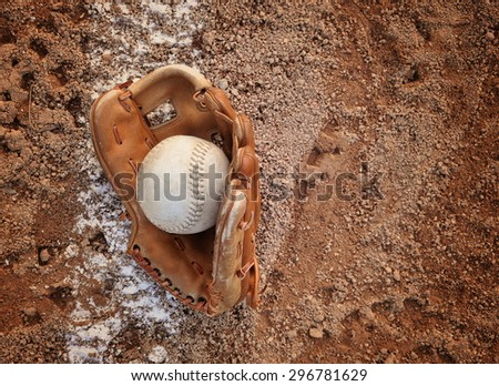 A closeup of an old baseball and glove on a dirt background with copyspace for a message for a sport or recreation concept. - stock photo