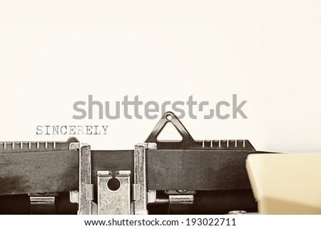 """A closeup of an old fashioned typewriter with the words """"SINCERELY"""" clearly visible. - stock photo"""