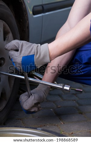 A closeup of changing a tire in a car