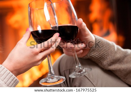 A closeup of cheering with glasses of red wine - stock photo