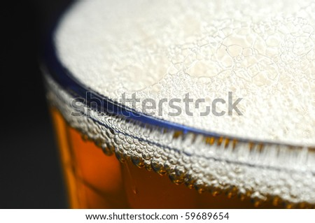 A closeup of dark beer in a cup with bubble suds at the top - stock photo