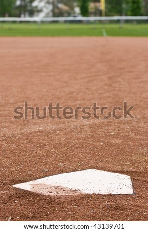 A closeup of home plate at a baseball diamond, looking out at the first base line towards the outfield. - stock photo