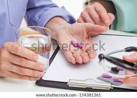 A closeup of pills and a glass of water - stock photo
