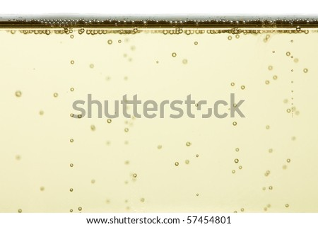 A closeup of some champagne bubbles rising to the top of a glass. - stock photo