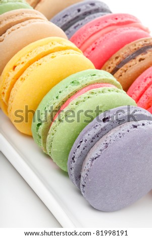 A closeup of some delicious french macaroons sitting on a white plate.. - stock photo