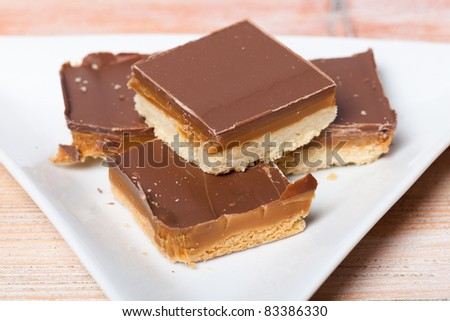 A closeup of some homemade chocolate and caramel millionaire's shortbread on a plate.