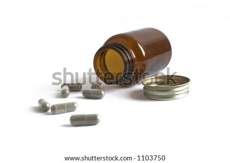 A closeup of some pills pouring out of a prescription bottle - stock photo