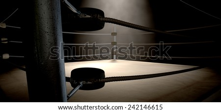 A closeup of the corner of an old vintage boxing ring surrounded by ropes spotlit by a spotlight on an isolated dark background - stock photo