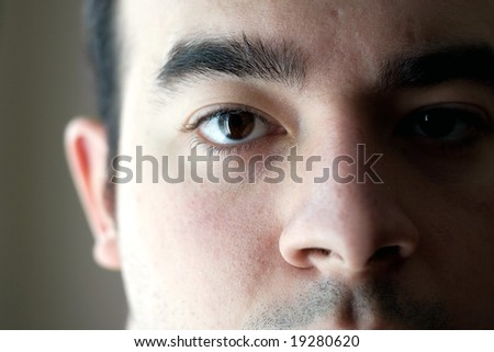 A closeup of the eye on a young man with a serious look on his face - stock photo
