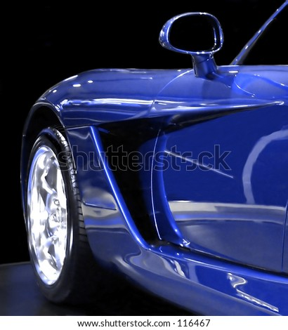 A closeup of the front quarter of a sportscar. - stock photo