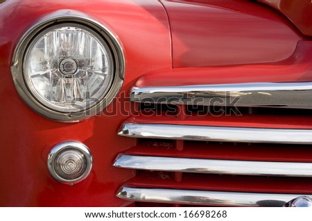 A closeup of the headlight and front bumper on a vintage car. - stock photo