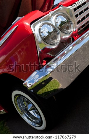 A closeup of the headlights and front bumper on a vintage American automobile. - stock photo