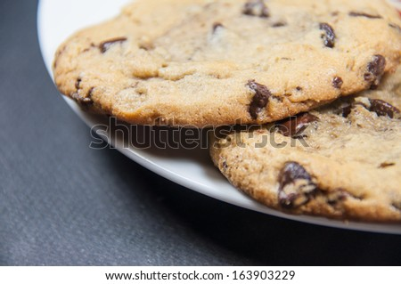 A closeup of two chocolate chip cookies on a plate - stock photo
