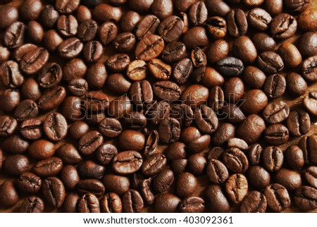 A closeup overhead view of several fresh coffee beans filling the whole frame of the image. - stock photo